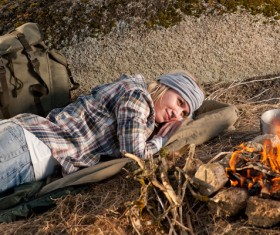 woman resting beside campfire Stock Photo