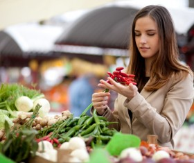 woman who buys chili in a vegetable stand Stock Photo