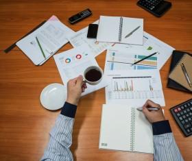 Businessman holding coffee sorting data Stock Photo