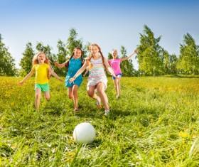 Children kicking the ball on the grass Stock Photo 01