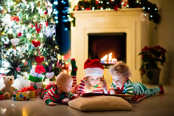 Children watching video in front of the Christmas tree Stock Photo 01