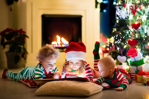 Children watching video in front of the Christmas tree Stock Photo 02