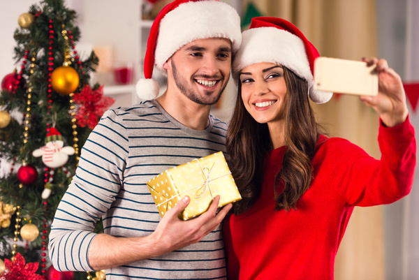 christmas couple taking photos with smartphone stock photo