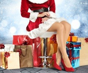 Christmas girl sitting on the chair and stacking gift boxes on the floor Stock Photo