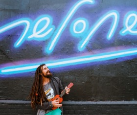 Fashionable man playing guitar under neon lights Stock Photo