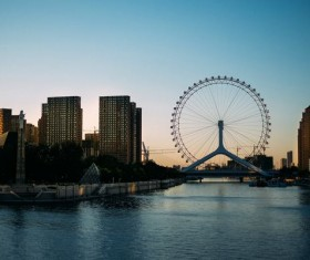 Ferris wheel across the river bank Stock Photo