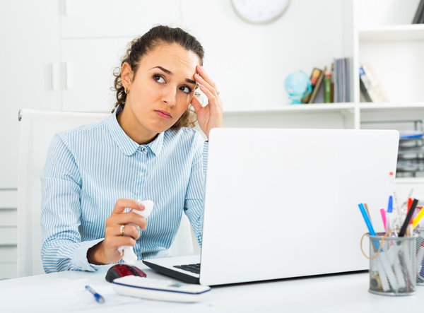 Unhappy businesswoman working at laptop in office