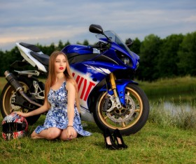 Girl and motorbike sitting on the grass Stock Photo