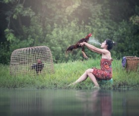 Girl holding a rooster in the river Stock Photo