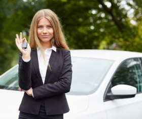 Girl holding car key in front of the car Stock Photo 02