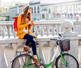 Girl sitting on bridge bar using smartphone to listen music Stock Photo