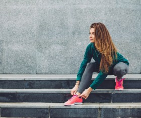 Girl tying shoes on the steps Stock Photo