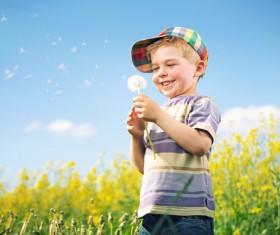 Happy little boy holding a dandelion flower Stock Photo