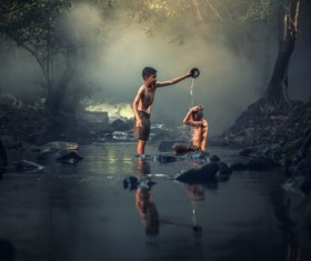 Help each other in the creek bathing kids Stock Photo