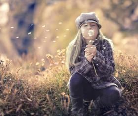 Little girl blowing dandelion flowers Stock Photo