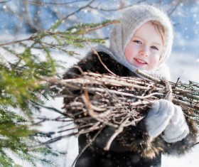 Little girl holding firewood outdoors in winter Stock Photo