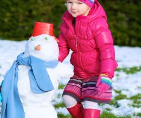 Little girl making snowman Stock Photo