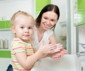 Little girl washing hands with mother Stock Photo