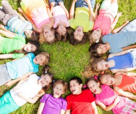 Lying in the grass in a circle of children Stock Photo
