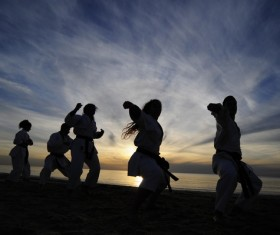 Men and women practicing martial arts in the early morning on the beach Stock Photo