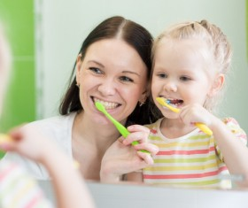 Mother teaching daughter brush teeth Stock Photo 02