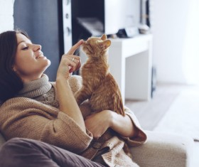 Sitting on the couch woman and pet cat Stock Photo