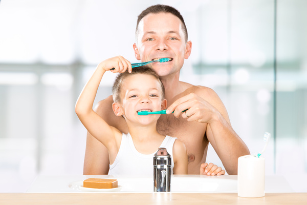 Smiling child brushes his teeth with dad Stock Photo 01