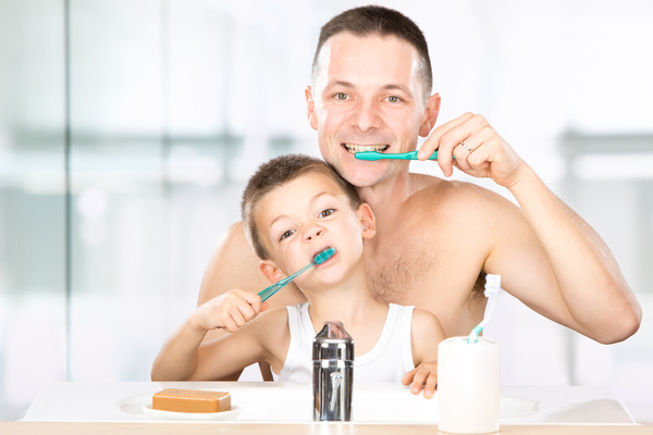 Smiling child brushes his teeth with dad Stock Photo 02