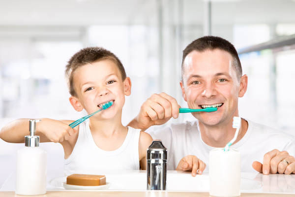 Smiling child brushes his teeth with dad Stock Photo 03