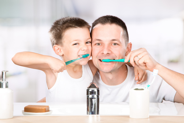 Smiling child brushes his teeth with dad Stock Photo 04
