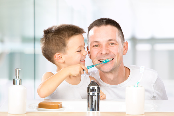 Smiling children help daddy brush his teeth Stock Photo