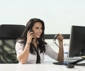 Smiling female boss answering the phone Stock Photo
