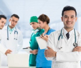 Smiling male doctor and medical team Stock Photo