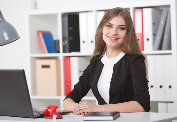 Hands on the table. Looking into the camera.Businesswoman sitting at a desk in the office right shoulder forward