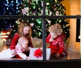 Three siblings looking at Christmas gifts Stock Photo