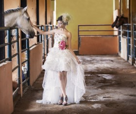 Wear fishtail wedding dress girl in horse barn Stock Photo