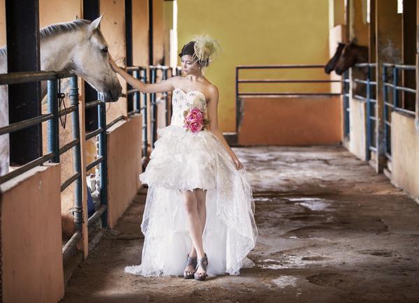Wear fishtail wedding dress girl in horse barn Stock Photo
