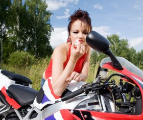 Woman applying lipstick with motorbike rear view mirror Stock Photo