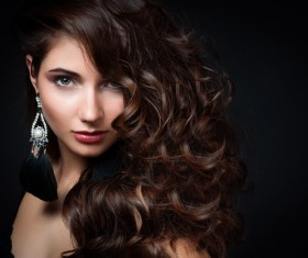 Woman with long curly hair wearing earrings Stock Photo