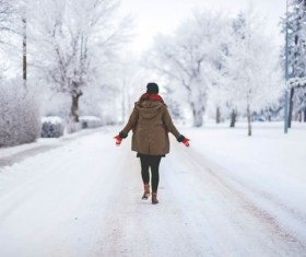 Women walking on snow covered roads Stock Photo