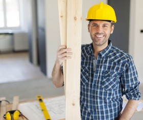 Workers holding wooden planks Stock Photo