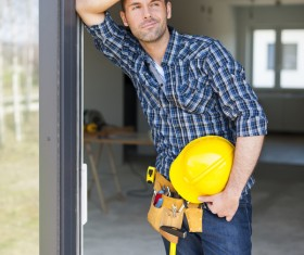 Workers leaning on the door frame to rest Stock Photo