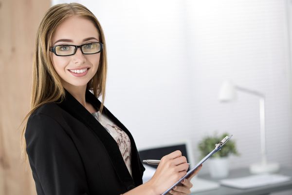 Young cheerful business woman standing with clipping board