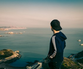 Young man watch sea scene on mountain Stock Photo