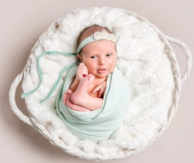 Baby lying in basket playing Stock Photo 01