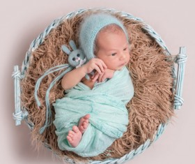 Baby lying in basket playing Stock Photo 02
