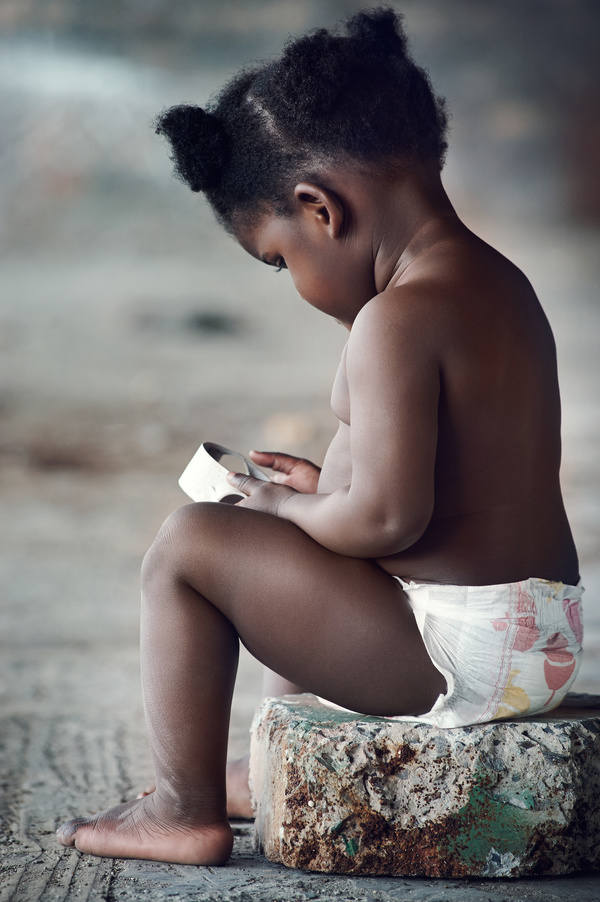 Black skin baby sitting on stone pier Stock Photo