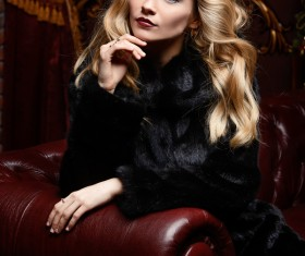 Blonde girl in black mink coat sitting on the couch Stock Photo 02