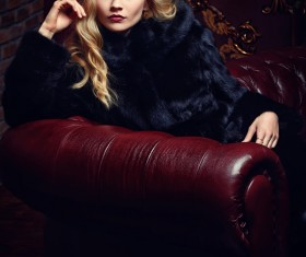 Blonde girl in black mink coat sitting on the couch Stock Photo 01