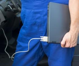 Car mechanic holding laptop Stock Photo